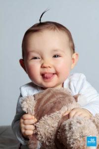 photo portrait d'un bébé avec sa peluche
