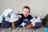 Photo grimace d'un bébé avec ses peluches sur un lit