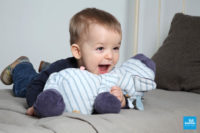 Photo d'un bébé sur un lit avec sa peluche