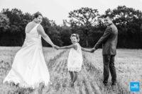 Photo des mariés et de leur fille dans un champs
