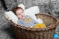 Photo d'un bébé dans un panier dans le décors paille du studio photo