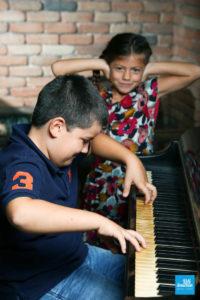 Photo humour d'un frère et sa sœur au piano