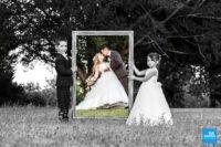 Photo de mariés avec leurs enfants tenant un cadre
