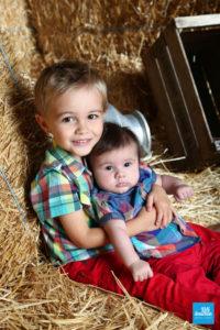 Photo d'un bébé et son grand frère sur un décors paille