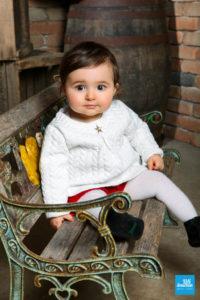 Portrait d'un bébé sur un banc dans les studios photo de Saintes