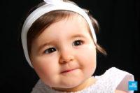 Portrait photo d'un bébé fille sur fond noir.