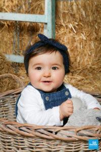 Bébé fille prise en photo dans une panière dans le décors paille du studio photo