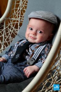 Portrait de bébé avec béret dans un fauteuil lors d'un shooting studio