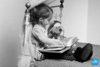 Photo d'une petit fille lisant une histoire à sa peluche lors d'un shooting photo à Saintes