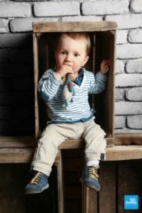 Petit enfant en shooting photo avec son doudou