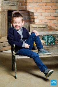 Portrait d'un petit garçon assis sur un banc
