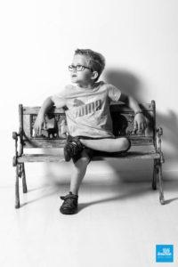 Portrait d'enfant sur un banc sur fond blanc