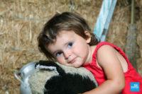 Petite fille en shooting photo sur un cheval à bascule