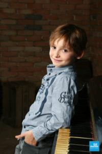 Portrait d'enfant accouder au piano