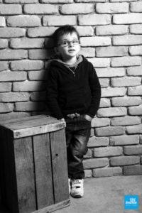 Photo noir et blanc d'un enfant sur fond brique