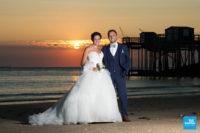 Photo de couple de mariage au coucher de soleil devant des carrelets