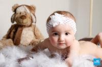Shooting studio photo d'un bébé dans les plumes et sa peluche