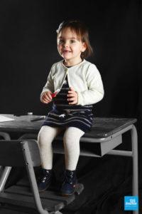 Photo d'une petite fille sur un table d'écolier