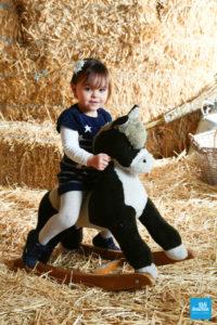 Petite fille sur un cheval à bascule dans les studio photo de Saintes