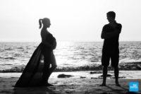 Photo de grossesse en couple et en extérieur sur la plage.