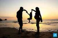 Photo de famille et de grossesse au bord de mer au coucher du soleil
