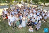 Photo de groupe de mariage devant une salle des fêtes