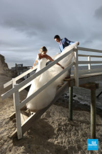 Photo de mariage d'un couple sur des carrelet au bord de la mer