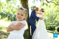 Photo de d'un couple de mariés et leur fille dans un parc