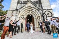 Sortie des mariés de l'église, haie d'honneur avec roue de vélo